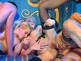 Blond and brunette shemales ride two guys dicks
